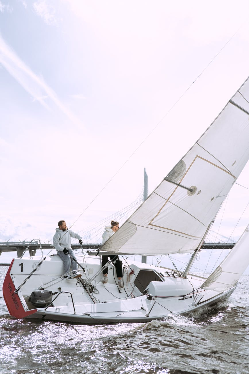 man in white t shirt and black pants standing on white sail boat